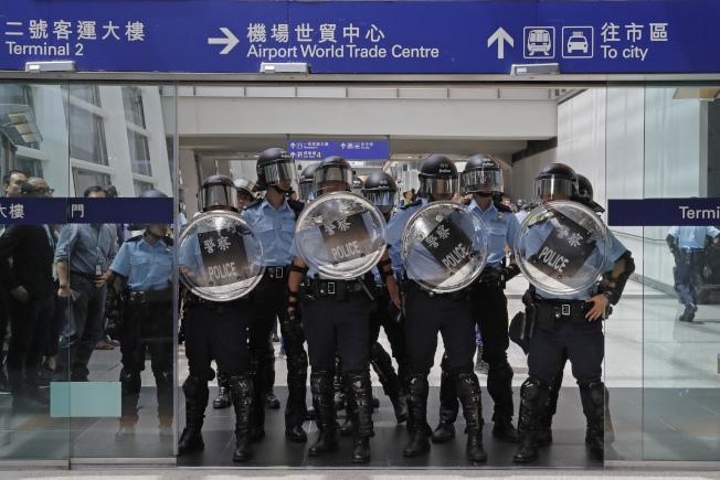 反送中活動已進行80多天,且愈演愈烈。已有香港民眾準備移民海外。圖為示威群眾1日堵塞機場交通,港警趕到機場,驅離示威者。(美聯社)