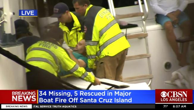 加州火燒船悲劇,五名船員獲救生還。圖為其中一名船員正被送往岸上。(美聯社)