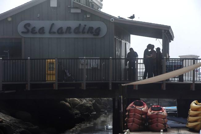 人們在岸邊辦公室等待船難搜救消息。(美聯社)