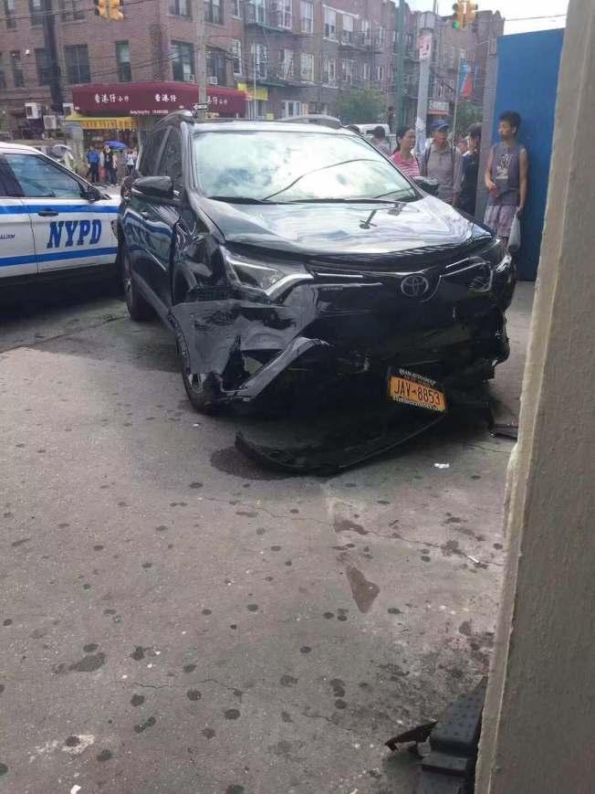 一輛黑色轎車日前失控撞向8大道地鐵站,車頭被撞毀。(讀者提供)