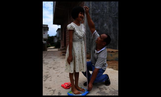隨著生活改善,大陸孩童的身高也顯著提升。圖為廣西上思縣南屏瑤族鄉醫師王衛江,正在為村裡的兒童量身高。(新華社)