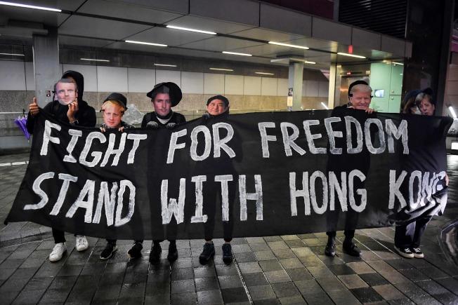 """香港青年举起标语,誓言""""争取自由,坚守香港""""。(Getty Images)"""