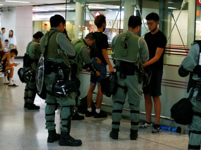為阻止示威者癱瘓機場交通的行動,香港警方在港鐵主要車站嚴查,要民眾出示身分證件及搜查隨身物品。(路透)