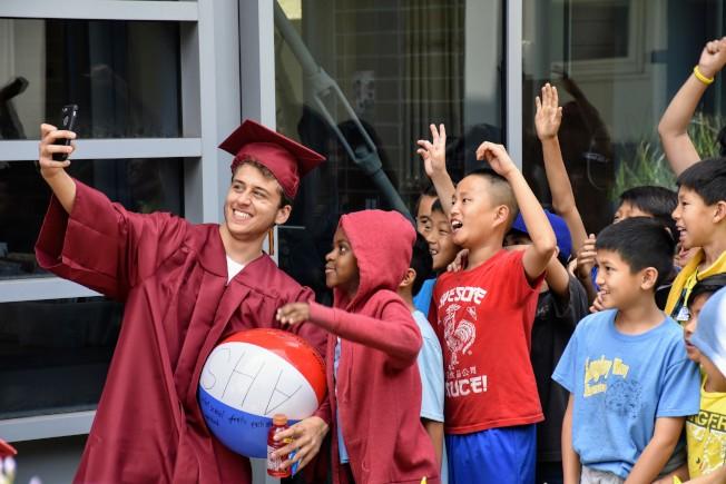 亞凱迪亞高中畢業生和小學生們玩自拍留念。(學區提供)