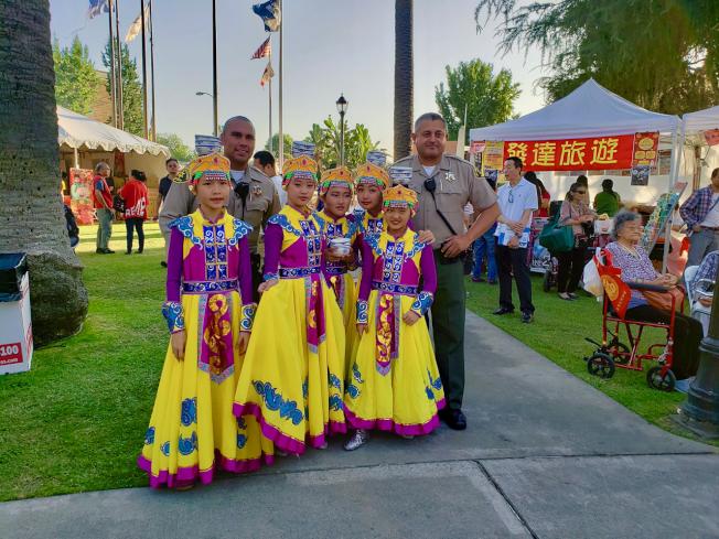 現場負責治安的洛杉磯縣警員,休息時間也觀看表演,圖為警員與羽翼舞蹈小演員們合影。(圖與文:記者陳開)