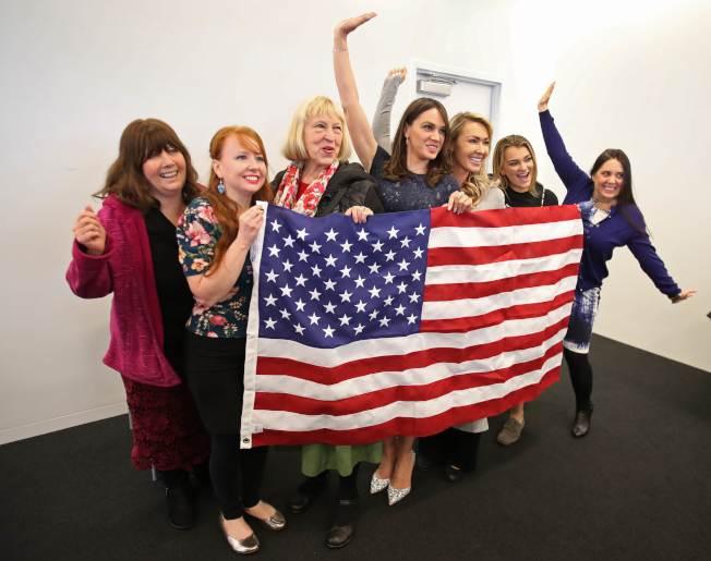 圖為新移民舉著美國國旗合影,慶祝成為美國公民。(Getty Images)