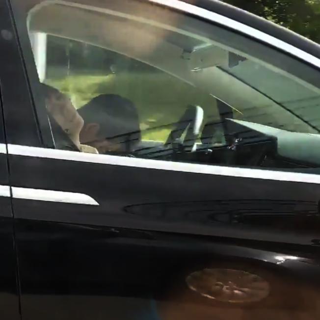 一輛特斯拉電動車8日在麻州高速公路行駛時,有人拍到駕駛人腦袋瓜垂在胸前呼呼大睡,旁邊乘客座上的人也在睡覺。(取自推特)