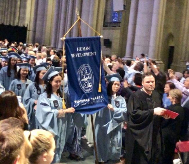 哥倫比亞大學師範學院畢業禮,女生身著禮袍舉著學院校旗登場。(校友周蕊提供)