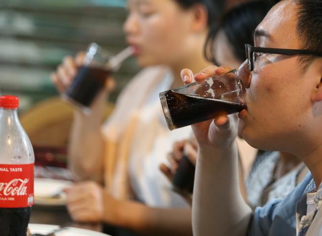 新近研究顯示,較矮的人糖尿病風險較高。圖為泰國曼谷小吃攤客人正在喝含糖飲料。歐新社