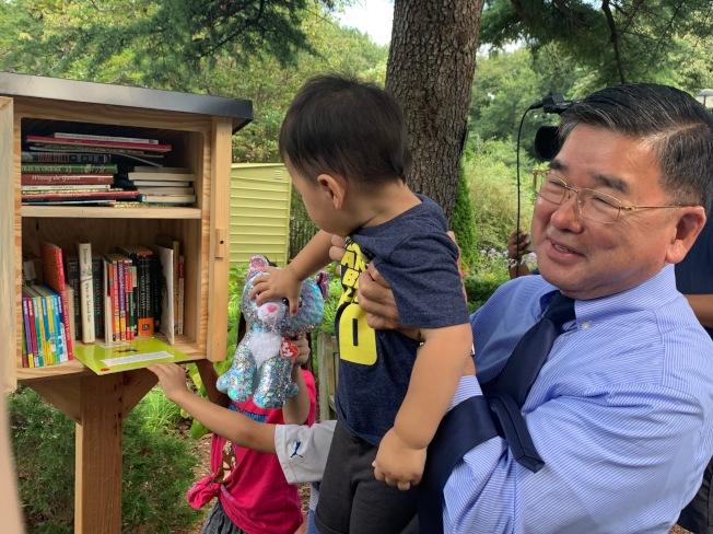 顧雅明出席「免費小圖書館」剪綵活動,並把適合各年齡層民眾閱讀的書籍置入小木箱中。(記者賴蕙榆/攝影)