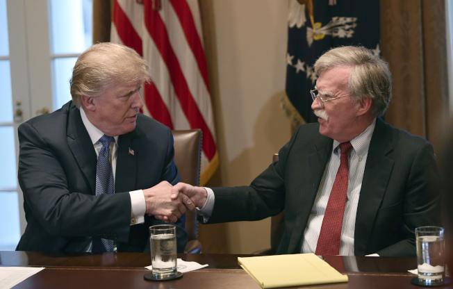 川普總統宣布開除國家安全顧問波頓,但波頓說是他先提辭呈。圖為波頓在白宮出席內閣會議與川普握手的資料照片。(美聯社)