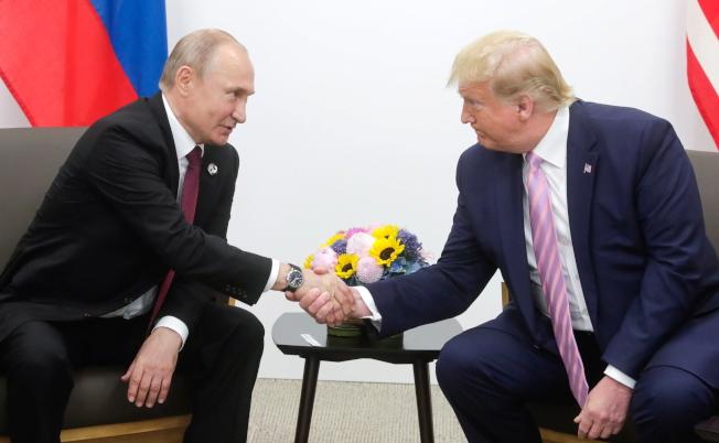 據說由於川普的幾句話露餡,華府急撤臥底俄羅斯總統普亭身邊的美國間諜。圖為普亭(左)和川普於今年6月在大版G20峰會見面。(歐新社)