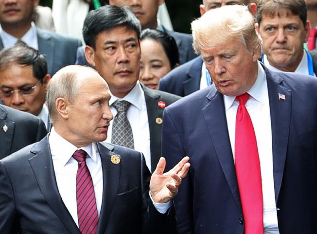 據說俄羅斯總統普亭(前左)辦公室的一名官員是美國間諜,圖為川普總統(前右)2017年在APEC會議與普亭見面。(美聯社)