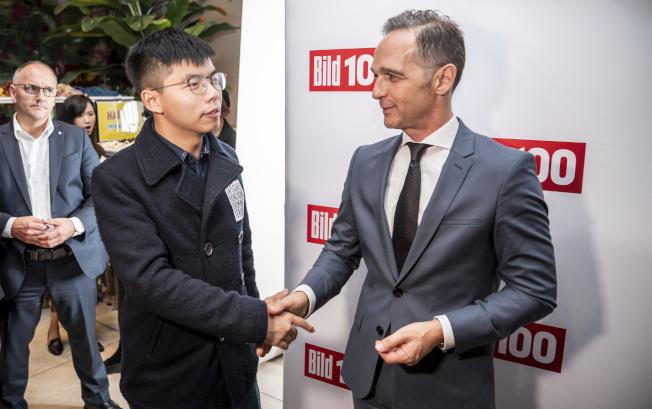 德國外交部長馬斯(右)與香港眾志祕書長黃之鋒見面談話。(美聯社)