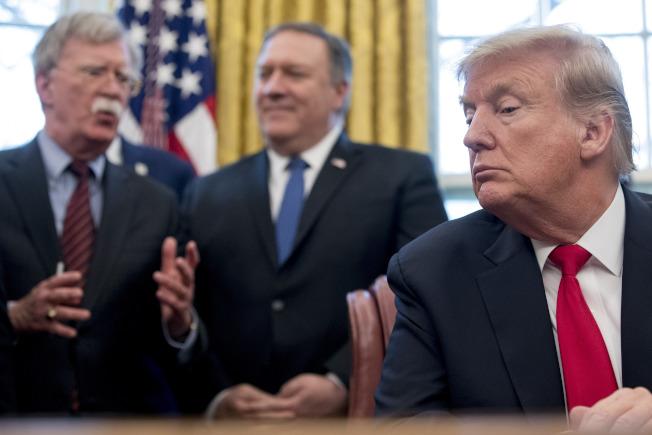 美國總統川普(右)10日推文宣布開除國安顧問波頓(左)。圖為波頓與國務卿龐培歐(中)今年2月在白宮等候川普簽署一項備忘錄。美聯社