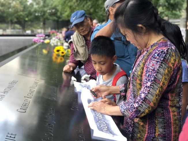家屬用鉛筆拓下逝去親人的名字。(記者張晨/攝影)