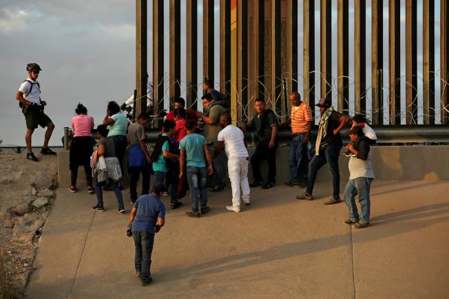 聯邦海關和邊境保護局(CBP)幹員在德州艾爾帕索(El Paso)一處邊牆旁,詢問非法入境的移民問題。(路透)