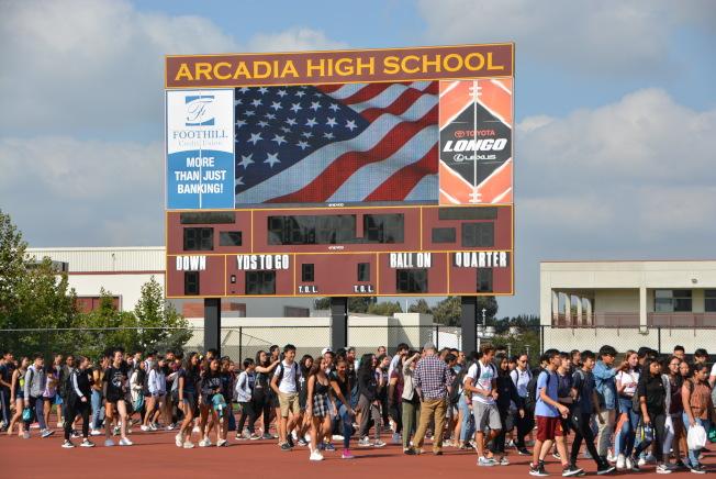 走過星條旗下,同學們進入運動場紀念九一一事件18周年。(記者丁曙/攝影)