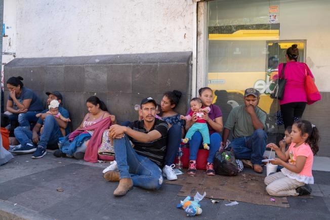 大部分是墨西哥人的無證移民,坐在華雷斯城的美墨邊界旁,等待伺機進入美國。(Getty Images)
