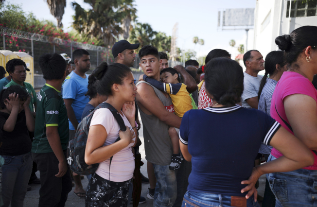 美國最高法院裁定,無證客不能在邊界申請政治庇護。圖為無證移民在墨西哥一邊排隊,等候伺機進入美國。(美聯社)