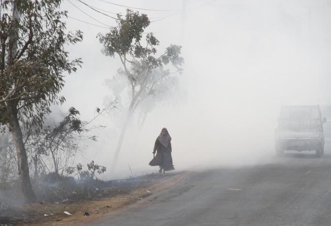 印度尼西亞南加加里曼丹森林火災,一名婦女沿著煙霧覆蓋的道路前進。(路透)