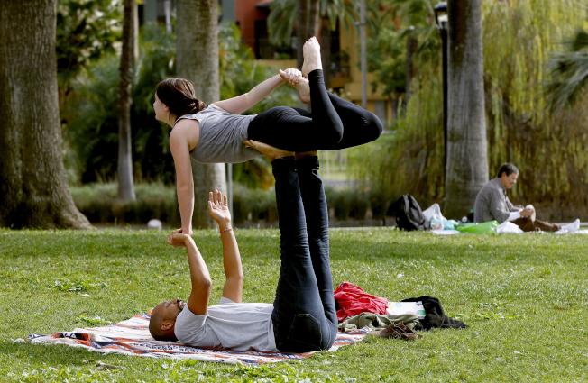 隨著氣候變遷引發更多劇烈天災,並造成受害者出現憂鬱症和創傷後壓力症候群等症狀,有些民眾尋求「創傷知情瑜珈」;圖中為洛杉磯民眾在公園做一般的瑜珈。(美聯社)