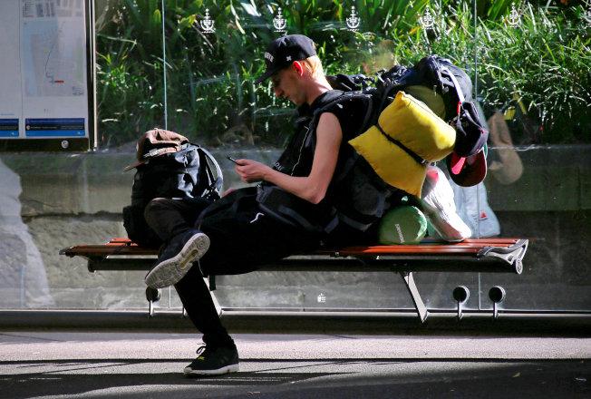 澳洲雪梨路邊的一名背包客在長凳上休息。(路透)