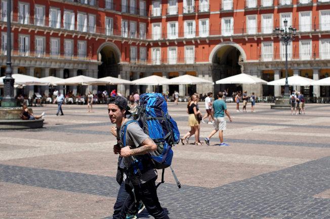 一名背包客遊歷西班牙馬德里主廣場。(路透)