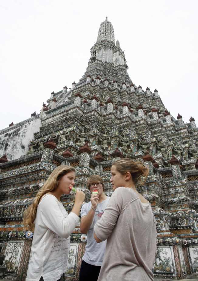 白人觀光客在泰國鄭王廟(Temple of the Dawn)旁吃冰消暑。(路透)