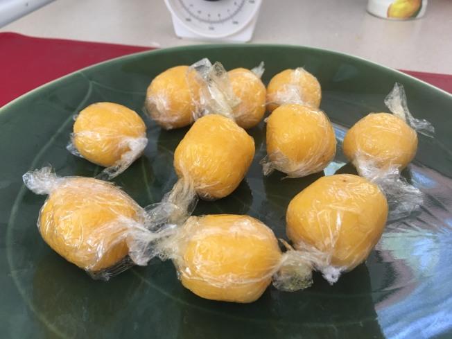 3.將植物油、椰蓉、糖粉及濾好的鹹蛋黃碎混合均勻,分成平均的10份。用保鮮膜包成小圓球,放入冰箱冷凍待用。