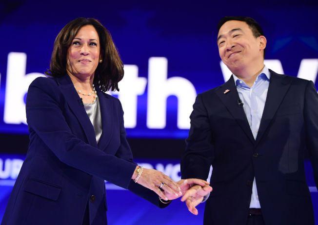 華裔參選人楊安澤(右)與人氣女將賀錦麗握手。(美聯社)