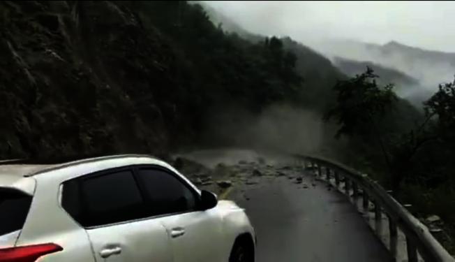 四川平武輔警及時喊停兩輛車,當車停下的剎那,兩三米遠的塌方處再次出現落石。(視頻截圖)