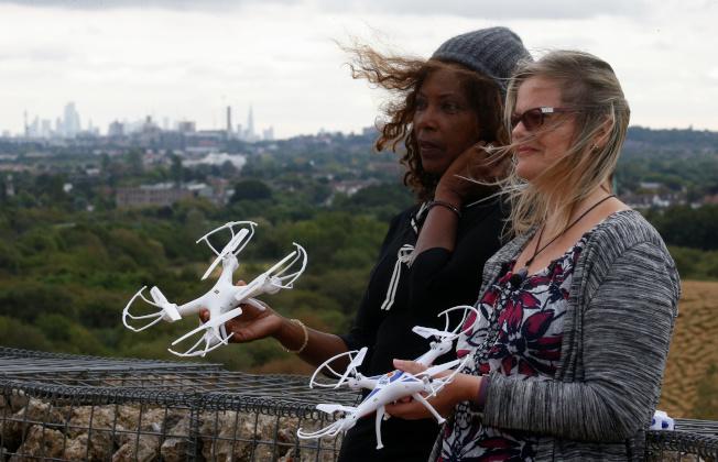 環保組織「希斯洛暫停」13日操控無人機干擾機場失敗。圖為兩名組織成員12日在機場附近手持玩具無人機合照。(路透)