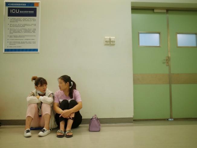 子寬的媽媽和姑姑坐在手術室旁等待子寬手術結束。(取材自新京報)