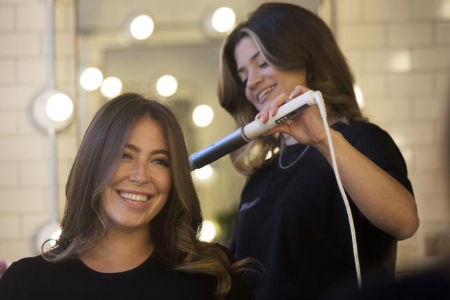 互相整理、修剪頭髮,比上髮廊給人做造型節省許多。(美聯社)