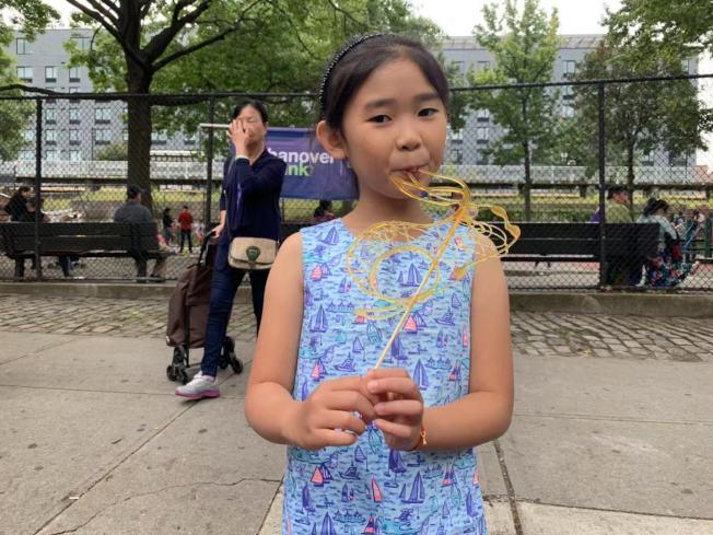 八歲柳艾寧第一次在街坊節上品嚐到糖畫。(記者牟蘭/攝影)