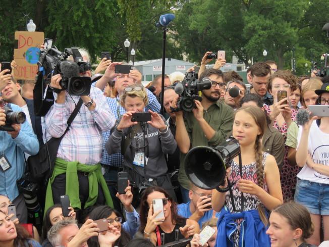 「氣候行動高峰會」23日將於紐約的聯合國總部召開,獲邀出席的瑞典環保小鬥士桑柏格(前排持麥克風)13日造訪美國華府,與上千名關心氣候變遷的人士在白宮附近遊行,呼籲群眾「永不放棄」。華盛頓記者張加/攝影