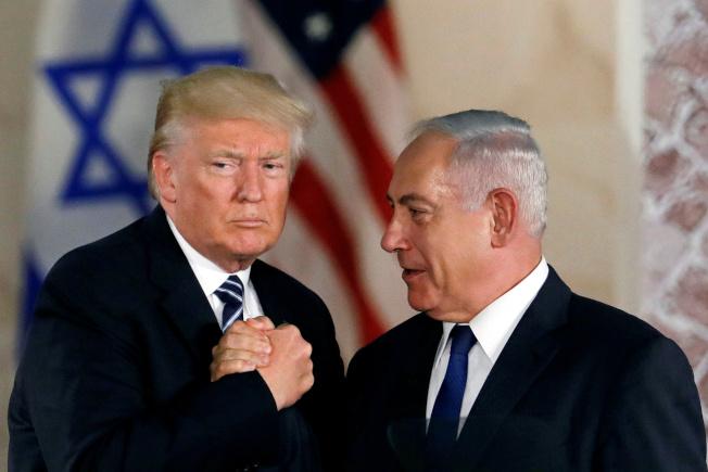 美國總統川普(左)14日表示,他已經與以色列總理內唐亞胡(右)通話,討論簽署共同防禦條約的可能性。圖為川普2017年5月訪問以色列時與內唐亞胡握手。(路透)
