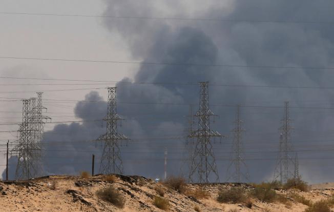 從遠處看,阿布蓋格煉油廠區冒出滾滾黑煙。(路透)