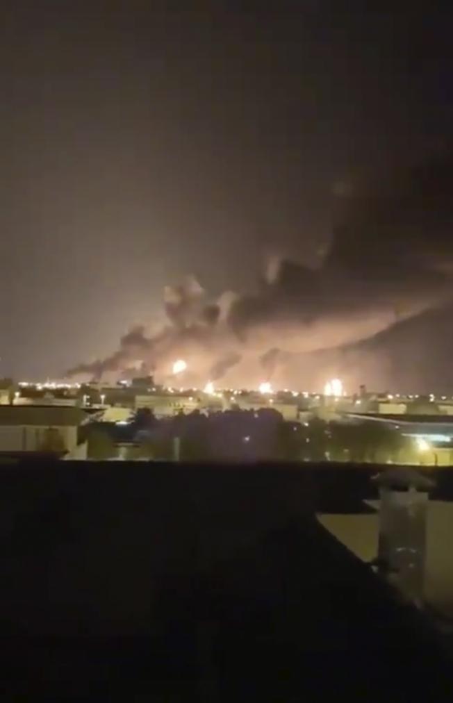 沙烏地阿拉伯兩處石油設施遭無人機攻擊,全球最大的煉油廠陷入火海。圖為阿國東部的阿布蓋格煉油廠在夜間冒出火光與濃煙。(路透)