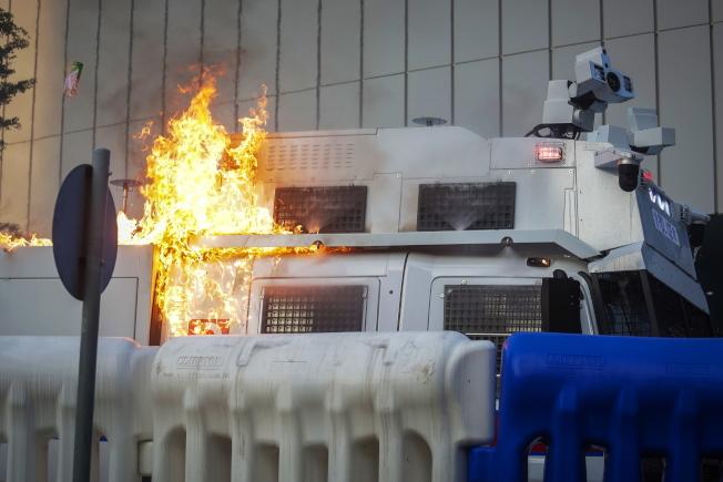 示威者15日對政府總部與特首辦投擲汽油彈洩憤,水炮車一度起火。(歐新社)