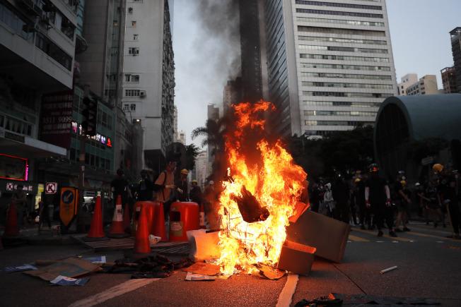 香港反送中示威者15日繼續抗議。在地鐵灣仔站前出現有人故意縱火。(美聯社)