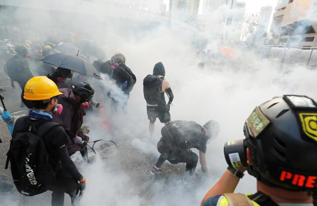 香港反送中示威者15日聚集香港政府總部,警方施放催淚煙驅離。(路透)