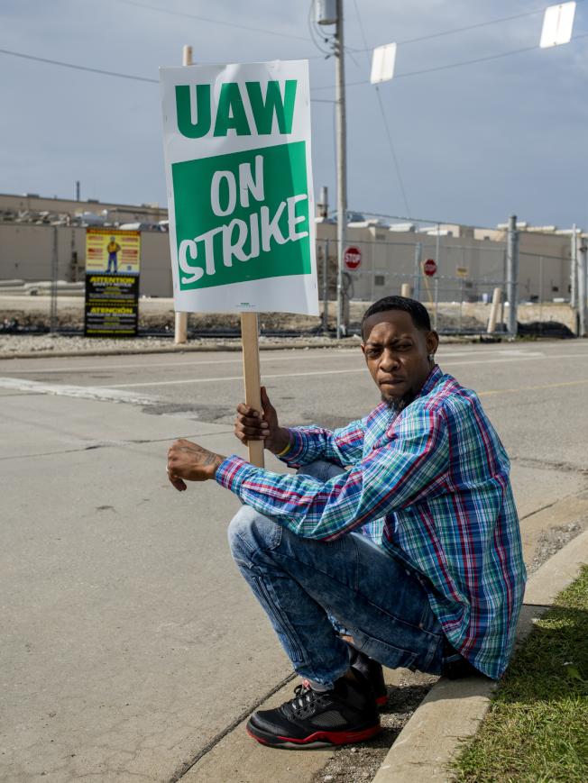 密西根州佛林廠的通用汽車廠工人諾伊李15日坐在廠外,加入汽車工人罷工行列。(美聯社)