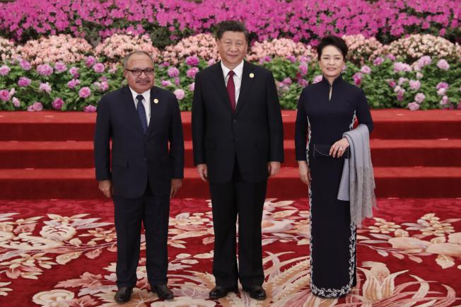 中國國家主席習近平和夫人彭麗媛4月在北京人民大會堂舉行宴會,歡迎出席一帶一路國際合作高峰論壇的領袖。圖為習近平夫婦(中、右)迎接巴布亞紐幾內亞總理奧尼爾(左)。(中新社)