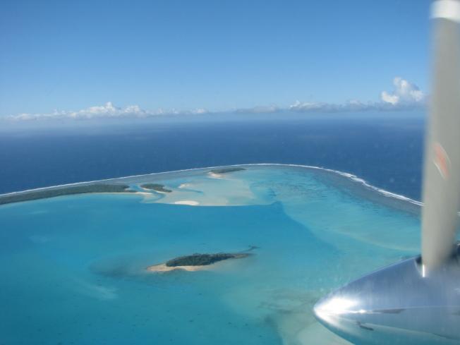 太平洋島國經濟發展緩慢,嚴重依賴外援。圖為一架飛機飛抵庫克群島一座潟湖上空。(美聯社)