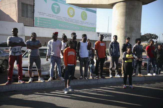 圖為準備在美國申請庇護的非洲移民 ,在墨西哥邊界城蒂華納等待被叫到號碼 。(美聯社)