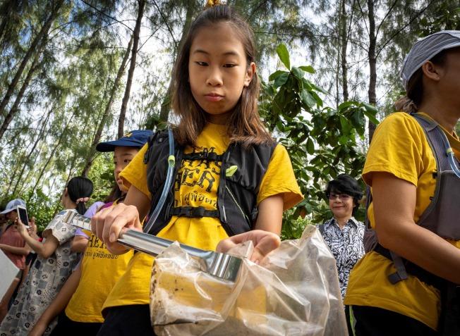 泰國12歲環保少女黎利(中)在曼谷清理塑膠垃圾。(Getty Images)
