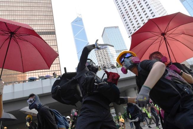 示威者15日向警察防線擲汽油彈及磚塊,警方施放催淚彈及以水炮車驅散。(中通社)