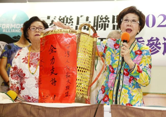 前副總統呂秀蓮(右)決定接受喜樂島聯盟及其他政黨推薦,參選總統,17日記者會上更秀出支持者以竹籃捐贈的大筆贊助金。(記者曾原信/攝影)
